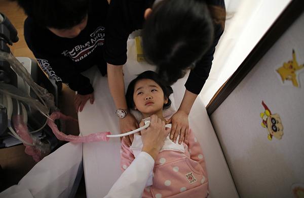 当地时间2014年2月27日,日本二本松,医护人员为5岁的日本女童做检查。 视觉中国 资料图