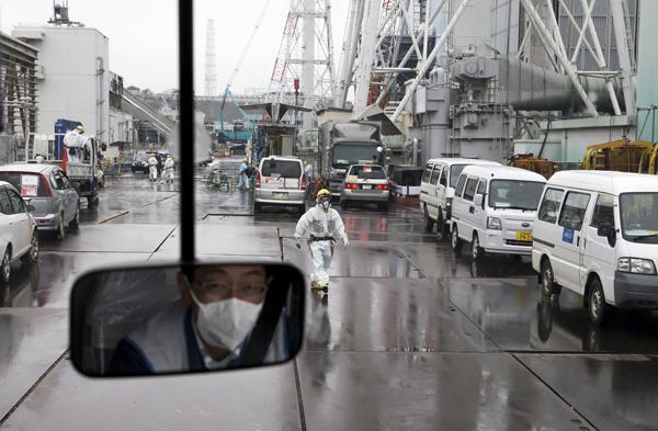 2017年2月23日,东京电力公司福岛第一核电站内一名身穿防护服、口戴口罩的工人看向汽车窗外。