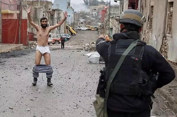 """这是3月4日,在摩苏尔瓦迪哈贾尔街头发生的""""寻常""""一幕。据路透社5日报道,图中这名恐慌的男子,为了证明自己不是自杀式炸弹袭击者,被勒令脱去自己的衣服。"""