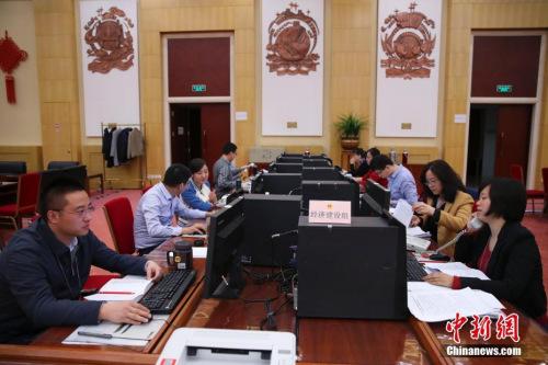 3月13日,十二届全国人大五次会议秘书处议案组,工作人员正抓紧对代表议案逐件进行分析。 中新社记者 刘震 摄