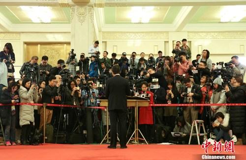 """3月12日,十二届全国人大五次会议在北京人民大会堂举行第三次全体会议,""""部长通道""""受到众多记者关注。 中新社记者 赵隽 摄"""