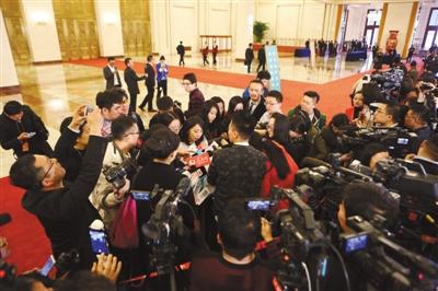"""3月3日,人民大会堂北门""""部长通道"""",大批记者在抢占最佳采访位置。新京报记者 侯少卿 摄"""