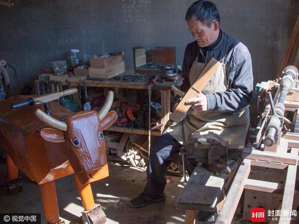 """吉林省吉林市永吉县西阳镇农民67岁的李景阳在家人的帮助下调试自己发明制造后经改良的""""木牛""""冰上拉爬犁的功能。"""