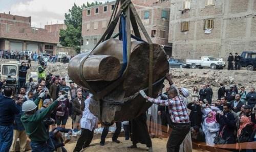 考古队小心翼翼的把雕像上半部吊起,吸引许多民众围观。