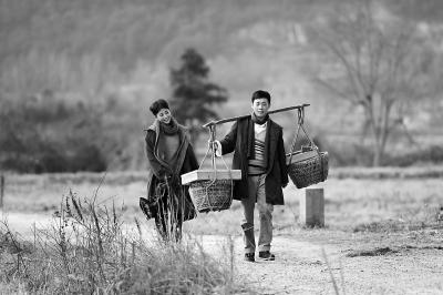 """剧中,张译饰演的陈江河(右)在骆玉珠(殷桃饰)的陪伴下挑着担子""""鸡毛换糖""""。"""