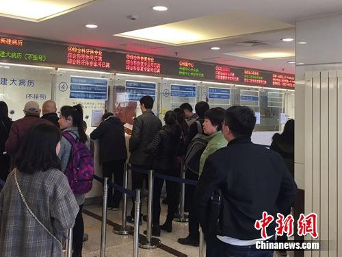 图为市民们在北京大学口腔医学院大厅排队挂号。吕春荣 摄