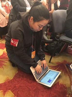 人民网记者朱一梵在现场跪着赶稿