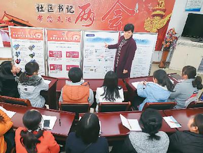 图为3月15日,在安徽省合肥市铜陵路街道花溪社区党员群众学习全国两会精神。