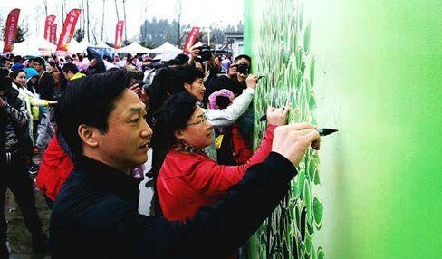 """领导嘉宾在""""我爱成都 健康成都 低碳环保 绿色出行""""签名树上签名"""