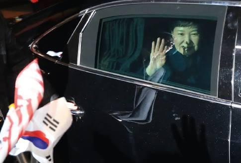 3月12日,朴槿惠乘车抵达位于韩国首尔三成洞的私邸并向支持者挥手。当晚,遭弹劾并被解除总统职务的朴槿惠搬出韩国总统府青瓦台,回到她的私宅。图/法新