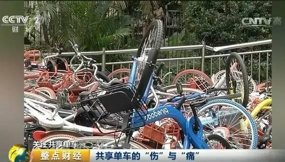"""记者来到现场,发现社区过道两侧堆积着各种品牌的共享单车, 两座""""小山丘""""将近3米高,粗略估计有300多台。由于堆放粗暴,一些单车的车轮发生变形,不少车把、车篮等零件散落在周围。"""