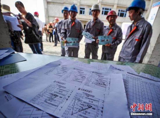 资料图:乌鲁木齐建筑用工企业展示为农民工发放工资的银行小票及缴纳工伤保险的复印件。刘新 摄