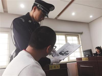 法警为被告人王某出示证据。昨日上午,被控涉嫌破坏计算机信息系统罪的王某在法院受审。新京报记者