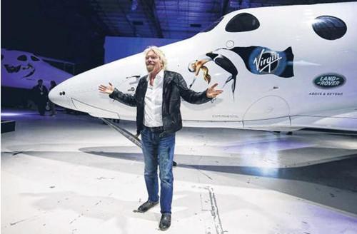 维珍集团创始人布兰森与可载送六名乘客上太空的太空船2号合影。(路透社)