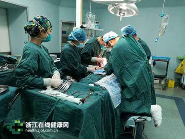 杭州市红十字会医院微创外科主任医师赵凯打着石膏的左腿以跪姿搁在凳子上,右腿单腿站立,在无影灯下做手术。 浙江在线健康网 图
