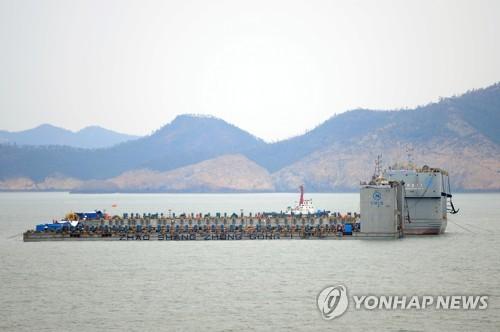 3月22日上午,在全罗南道珍岛郡东巨次岛海域,上海打捞局的2艘驳船准备抬起沉船(韩联社图)