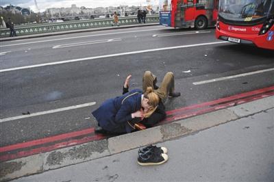当地时间22日,二次元什么意思英国伦敦恐怖袭击发生后,二次元什么意思一名行人在救助一名躺在地上的伤者。