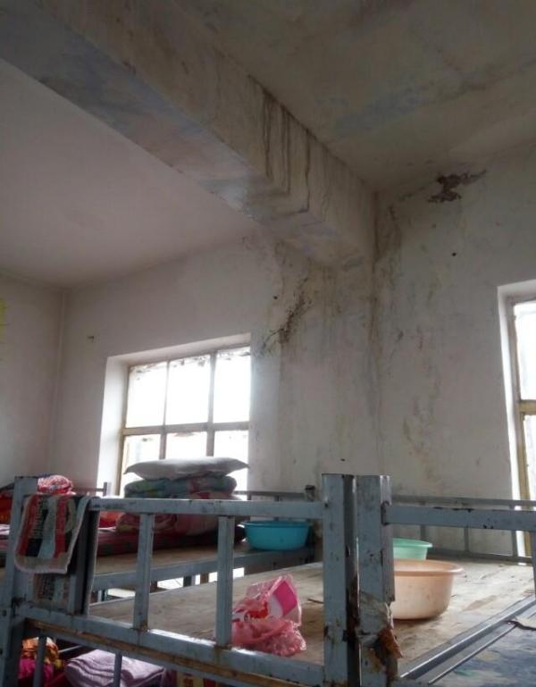山西长治壶关县南洋育栋学校小学部学生宿舍漏雨,学生用脸盆接水。