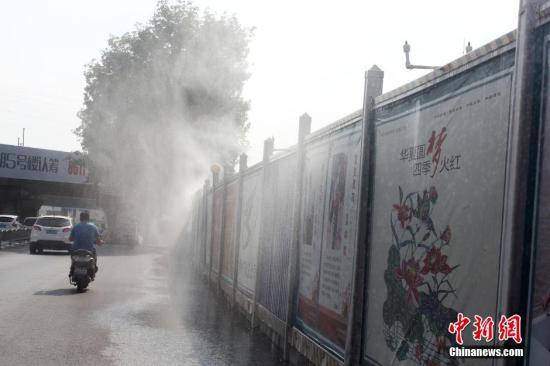 郑州金水路立交桥一施工工地隔挡板周围,咸鱼怎么做好吃安置了近30个水龙头喷洒水雾降尘。 马义恒 摄