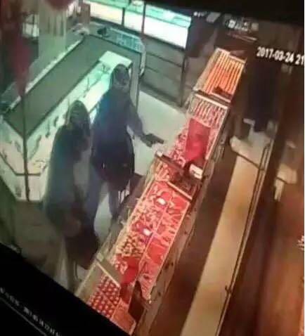 3月24日晚上10时左右,广西梧州市河东一黄金店发生一起抢劫案,两名戴着摩托车头盔的男子进入店内,一人手上疑似拿着枪支,实施抢劫。劫匪好大的胆子,公然上演现实版黄金大劫案。图为男子手上拿着枪状物实施抢劫。来源:梧州资讯