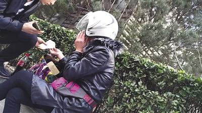3月14日,金台夕照地铁站附近,贷款中介员工从一中年女子(右)处购买假章。
