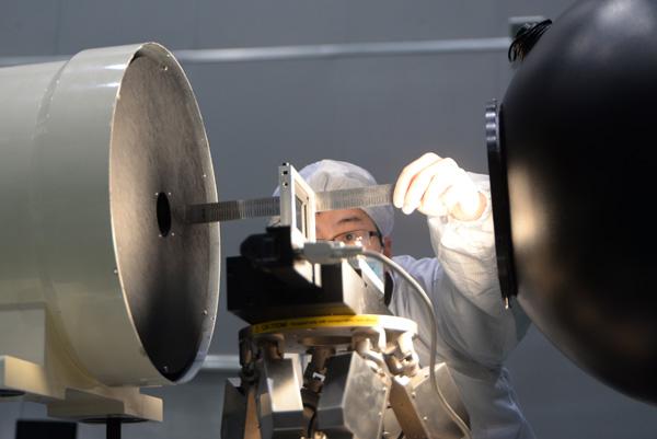 卫星研制人员在测量试验设备。