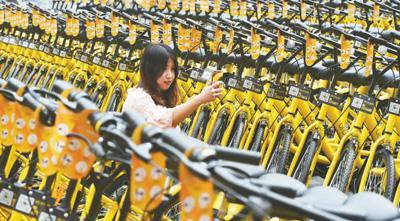 重庆地铁一号线尖顶坡站旁,市民使用手机扫码取车。