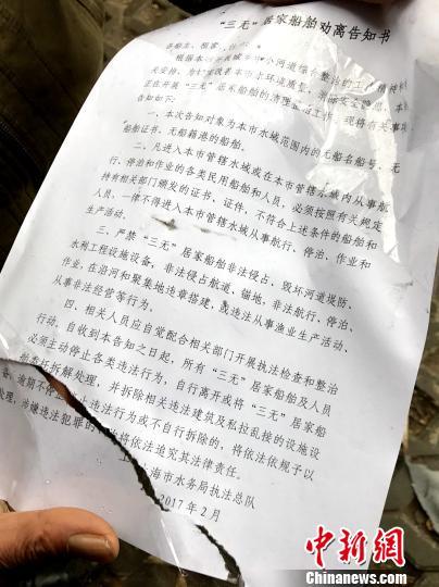 """住户将2017年2月上海市水务局执法总队发放给他们的""""劝离告知书""""展示给记者看。 王子涛 摄"""
