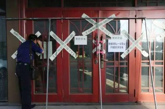 一名外地购房者在明珠湾楼盘销售中心外向内观看。