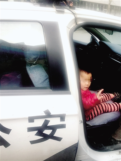坐上警车的孩子不忘摆手说再见