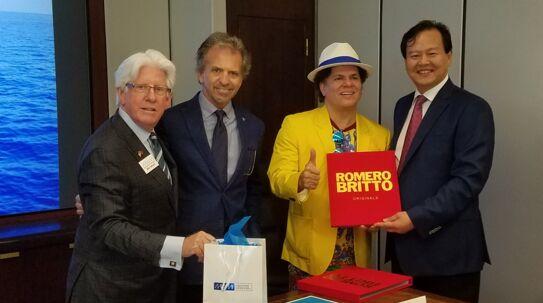 艺术家罗布里托(右二)向李浩杰赠送艺术品