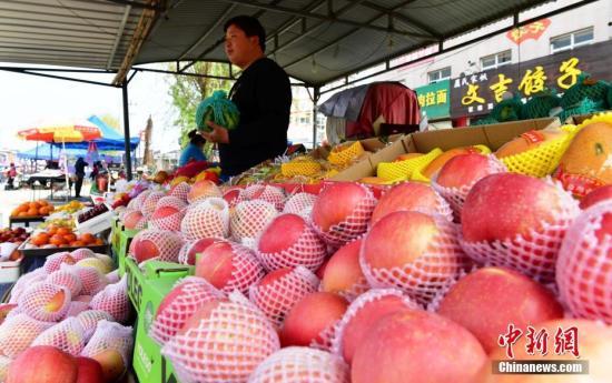 河北安新县一集市上的水果摊主正在忙碌。 中新社记者 翟羽佳 摄