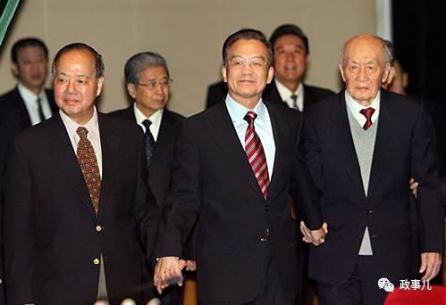 图:温家宝同李政道(左)和朱光亚手握手一同走上主席台