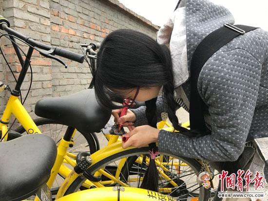 李冬雨在北京街头为被划掉多位数字的共享单车补牌。中国青年报中青在线记者 李想/摄