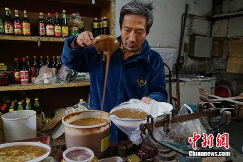 王老板在给顾客舀酱。中新网记者 李卿 摄