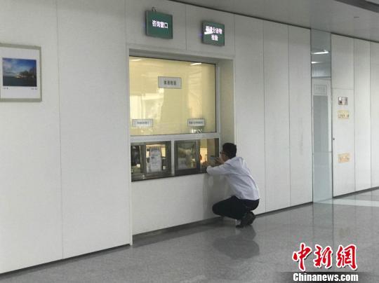 图为医院体液检验窗口,患者需要蹲着与医生沟通。 张枭 摄