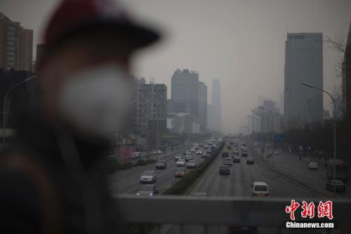 资料图:2021-02-26,北京市民在雾霾中出行。中新社记者 刘关关 摄
