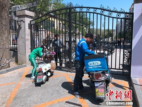 2017年4月21日,北京交通大学南门附近,由于快递电动车无法进入校园,一名学生隔着铁门取外卖。潘心怡 摄