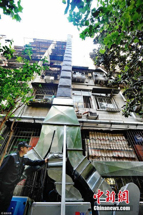"""现在,城管部门帮忙装好的净化装置远看像""""埃菲尔铁塔"""",烟道高约24米,伸出八层楼的房顶,为三家餐馆共用,二楼以上的烟道全部包裹着隔音棉,对居民生活造成的影响被降到最低。视觉中国"""