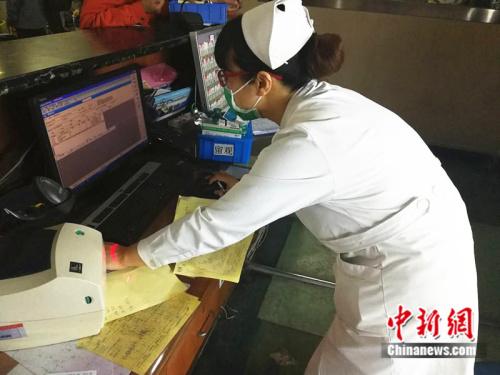 护士李伟正在核对患者的药物 中新网记者 张尼 摄