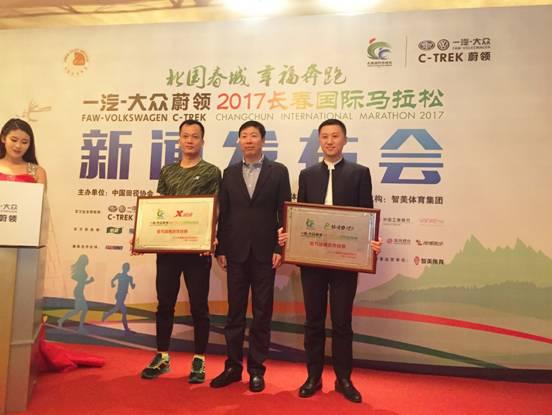 长春市体育局副局长赵晓路(中)为官方战略合作伙伴授牌