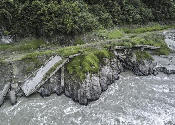 位于震中牛眠沟的百花大桥,在地震中被大自然的力量扭成麻花状,如今渐渐被泥石流以及河床掩盖。 视觉中国 图