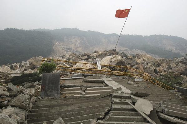 2008年5月,四川北川羌族自治县,北川中学新校区被覆没,曾经的喧嚣成了死寂,只有一杆红旗竖立在乱石之上。 澎湃新闻 资料