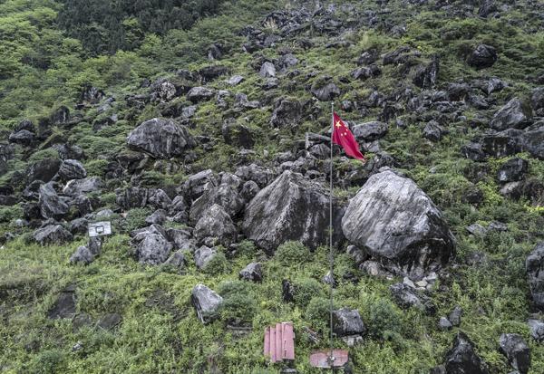 景家山在地震时崩塌,巨大的山石将北川中学新区茅坝中学整体掩埋,只剩一支国旗杆和一个篮球架,上千名师生遇难。 视觉中国 图