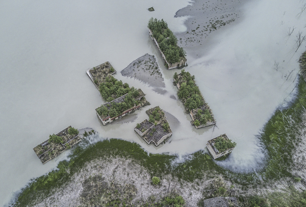 地震后形成的唐家山堰塞湖将北川县漩坪乡完全淹没,直至近些年水位退去后,才见到部分建筑的屋顶。 视觉中国 图