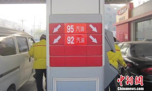 资料图:中国石油一座加油站工作人员张贴清晰的国五油品标识。 胡仁伟 摄