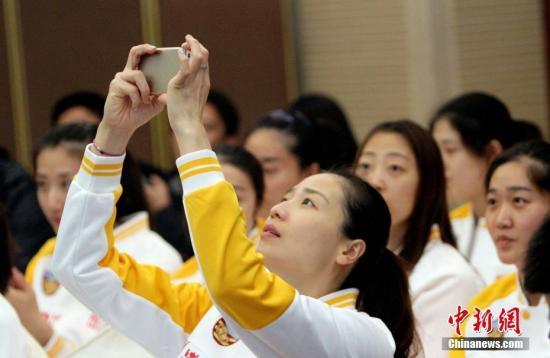 资料图:魏秋月用手机为两名外援拍照。中新社记者 张道正 摄