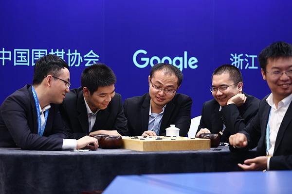 """在比赛过程中,围棋""""天团""""内部气氛相对轻松,讨论热烈,不过局势严峻。比赛进行到1个小时,""""天团""""内部就多次陷入讨论和矛盾,耗时过长。其中有个插曲是,周睿羊起身应该是去洗手间,为AlphaGo执棋黄世杰博士露出了""""迷之微笑""""。陈耀烨赶紧过去帮忙落子节约时间。"""