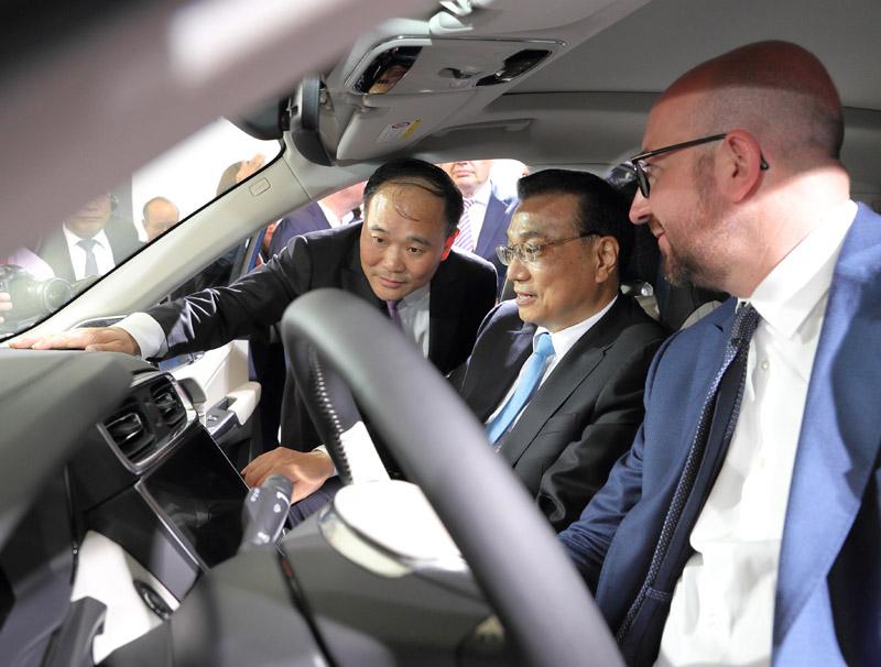 """李克强总理坐在车内,另一侧坐着比利时首相米歇尔。而探身进车为这一""""豪华乘客阵容""""讲解的,是吉利集团总裁李书福。"""