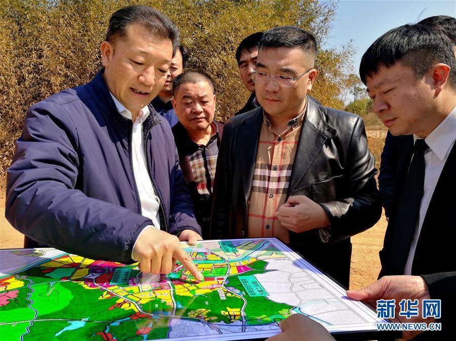 资料图:廖俊波(左一)向前来考察的企业代表介绍武夷新区发展规划(2月15日摄)。 新华社发